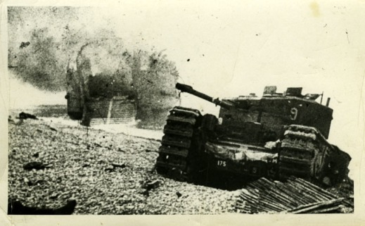 "Calgary Tanks Churchill ""Blossom"" of 9 Troop, B Squadron commanded by Lt. Marcel J.A. Lambert sits where it had broken its track in the chert after swerving off the wooden chespaling, designed to give the tanks traction in the loose stones. Behind Blossom, Tank Landing Craft No. 5 burns. Source: Dieppe Through the Lens, Hugh G. Henry Jr./After the Battle. Rob Alexander collection."
