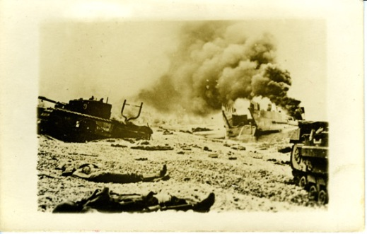 TLC 5 burns flanked by a pair of Churchills from the Calgary Tanks. The bodies of a Canadian and a U.S. Army ranger lie on the beach. Rob Alexander collection.