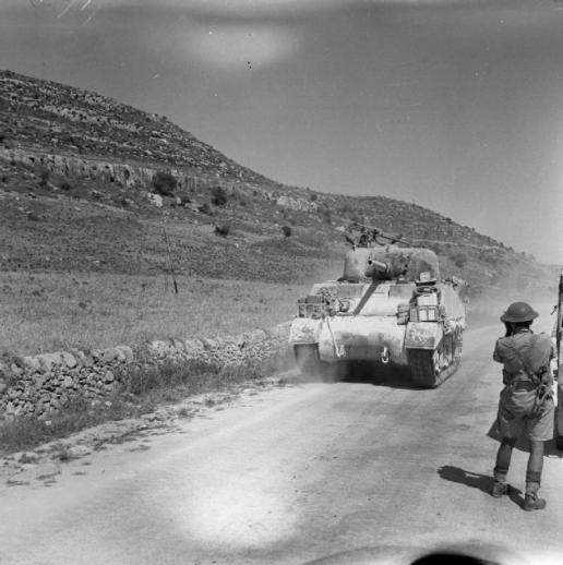 A member of the AFPU photographs a Sherman tank passing along a road, 12 July 1943.