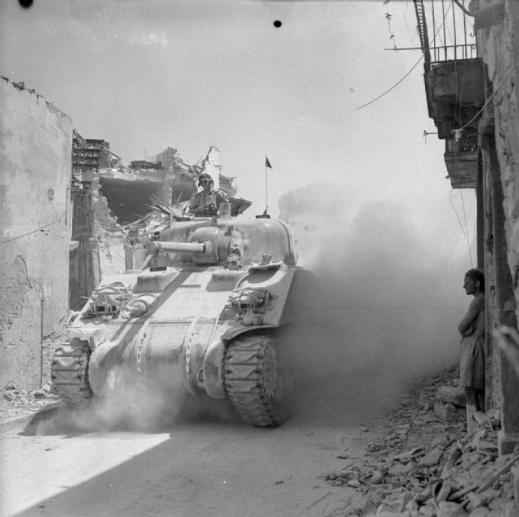 The Drive for Messina 10 July - 17 August 1943: A Canadian Sherman tank passes through a bomb scarred street in Regalbuto.  © IWM (NA 5592)