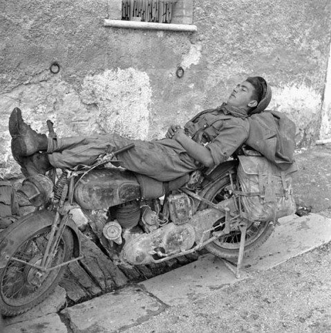 Trooper A.A. Coulombe, 14th Armoured Regiment (The Calgary Regiment), resting on motorcycle. Credit: Jack H. Smith / Canada. Dept. of National Defence / Library and Archives Canada / PA-144104