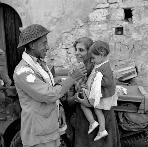 Trooper Ralph Catherall of The Calgary Regiment giving food to an Italian child, Volturara, Italy, 3 October 1943. Credit: Lieut. Jack H. Smith / Canada. Dept. of National Defence / Library and Archives Canada / PA-144105