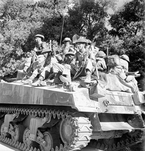 'Sherman' tank of the 14th Armoured Regiment (The Calgary Regiment) leading troops of the West Nova Scotia Regiment across diversion around blown bridge. Credit: Canada. Dept. of National Defence / Library and Archives Canada / PA-144114