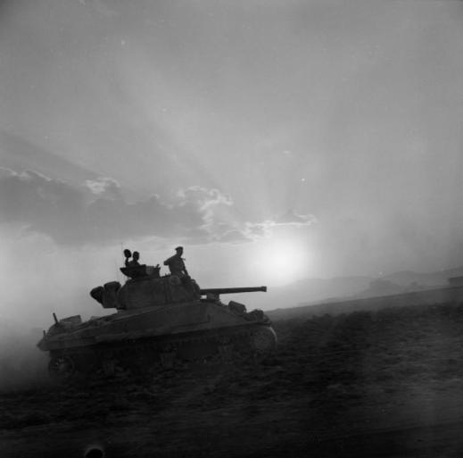 A Sherman tank of 'A' Squadron, 50th Royal Tank Regiment, silhouetted by the setting sun, 1 August 1943. © IWM (NA 5424)
