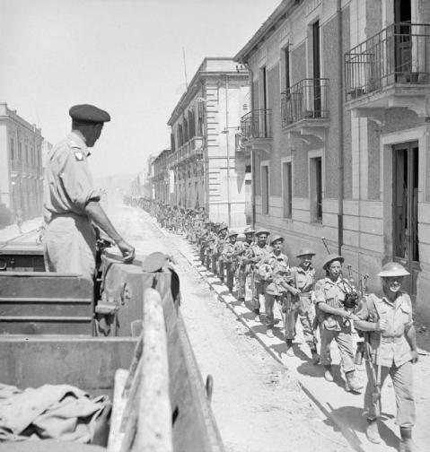 Personalities: The Commander of the Eighth Army, Lieutenant General Sir Bernard Montgomery, watches troops as they pass through the streets of Reggio. Personalities: The Commander of the Eighth Army, Lieutenant General Sir Bernard Montgomery, watches troops as they pass through the streets of Reggio. © IWM (NA 6220)