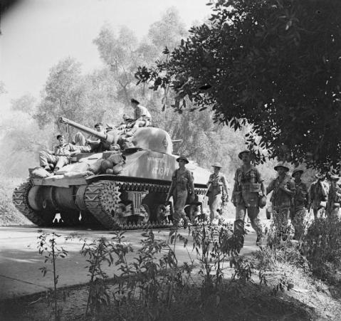 Reggio, 3 September 1943 (Operation Baytown): A Sherman tank and infantry advance north from Reggio. Although the Eighth Army encountered little active resistance during their advance, the natural obstructions of the terrain, combined with German demolition's resulted in very slow progress and prevented the Army from intervening in the fighting at Salerno until after the Germans had started to withdraw. © IWM (NA 6560)