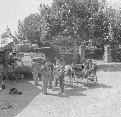 A Sherman tank crew from the Scots Greys chat to RAMC personnel travelling in a pony and trap, 12-13 September 1943. © IWM (NA 6833)