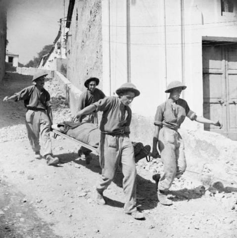 Stretcher bearers carry a wounded soldier to an advanced dressing station in Salerno, Italy, September 1943. © IWM (NA 7079)