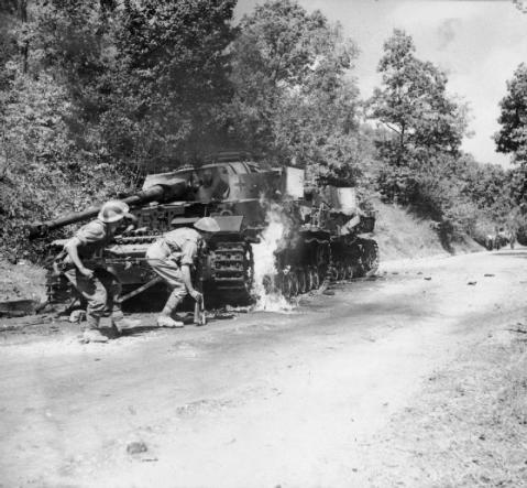 Men of the 2/6th Queens's Regiment advance past a pair of burning German PzKpfw IV tank in the Salerno area, Italy, 22 September 1943. © IWM (NA 7137)