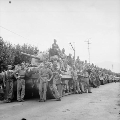 A line of Sherman tanks and their crews await the order to mount up and advance, September 1943. © IWM (NA 7250)