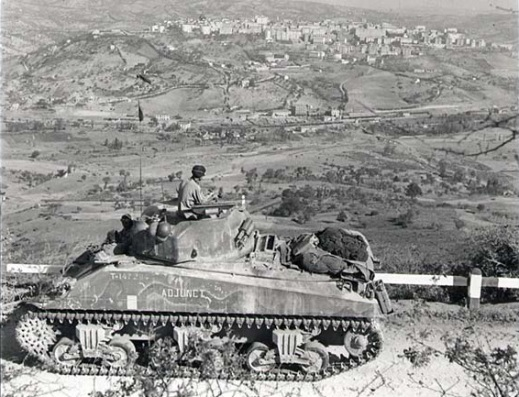 'Sherman' tank 'Adjunct' of 'A' Squadron, 14th Armoured Regiment (The Calgary Regiment), firing on Potenza in support of the advance of the West Nova Scotia Regiment.  Credit: Alexander M. Stirton/Canada. Dept. of National Defence/Library and Archives Canada/PA-144103