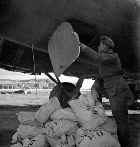 Unloading of the first load of airmail for Canadian soldiers in Italy from a Boeing B-17 aircraft of No.168(HT) Squadron, Royal Canadian Air Force, Foggia, Italy, 30 December 1943.   Credit: Lieut. Frederick G. Whitcombe / Canada. Dept. of National Defence / Library and Archives Canada / PA-140094.