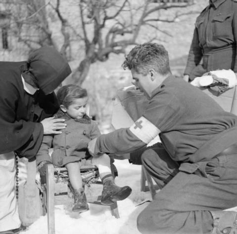 A medic bandages the leg of a small child in Casola Valsenio, 30 January 1945.