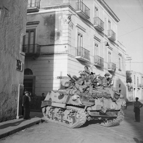 Sherman tank of the Scots Greys carrying troops of the 1/6th Queen's Regiment during mopping up operations in Torre Annunciata, 1 October 1943. © IWM (NA 7347)