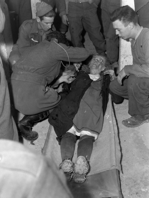 Major P.K. Tisdale treating a wounded Italian woman at the Advanced Dressing Station of No.4 Canadian Field Ambulance, Royal Canadian Army Medical Corps (R.C.A.M.C.)., San Vito di Ortona, Italy, 15 January 1944. Credit: Lieut. Alex M. Stirton / Canada. Dept. of National Defence / Library and Archives Canada / PA-114038