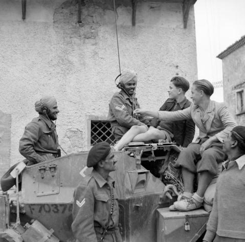 A scout car crew of 6th Duke of Connaught's Own Lancers, Indian Armoured Corps, chat with youngsters in San Felice, during the advance towards the River Sangro. © IWM (NA 8592)
