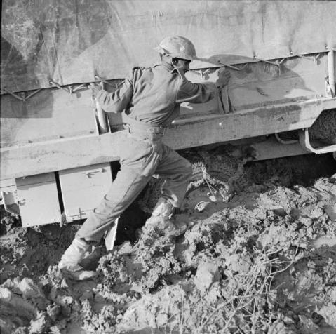 The Sangro River November 1943: An Indian soldier pushing his vehicle which is bogged down in deep mud in the Sangro area. © IWM (NA 8925)