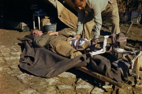 A Reception Officer at an Advanced Dressing Station examines a casualty wounded in the leg to determine whether a blood transfusion is required. One of a series of photographs showing the procedure when a casualty leaves the Regimental Aid Post. Field Transfusion Units working in conjunction with Advanced Dressing Stations saved many lives. © IWM (TR 2406)