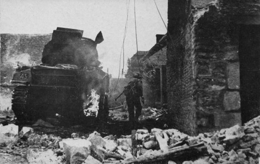 St. Lambert-sur-Dives, August, 1944 A soldier of the Argyll and Sutherland Highlanders of Canada, shovel on back, runs forward past a burning Sherman tank in the village street. Source.