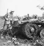 Private G.C. Butcher, 48th Highlanders of Canada, examines the wreckage of a German PzKpfW III tank destroyed by the Calgary Regiment, San Leonardo di Ortona, Italy, 10 December 1943.  Credit: Lieut. F.G. Whitcombe, Canada. Dept. of National Defence / Library and Archives Canada / PA-205251