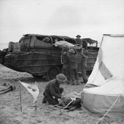 A casualty being loaded into a DUKW on the beach at Fossacesia, 15 December 1943. © IWM (NA 9891)