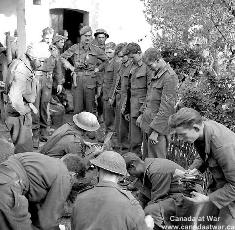 Infantrymen of The Seaforth Highlanders of Canada searching German prisoners on the Moro River front, Italy, 9 December 1943. Canada at War.