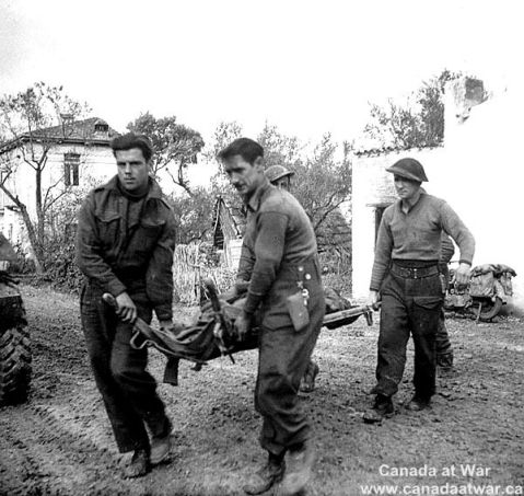 Soldiers of the 1st Canadian Division carry a dead comrade killed by shell fire while escorting German prisoners. None of the prisoners was killed. 10 Dec 1943, San Leonardo di Ortona, Italy. Canada at War.