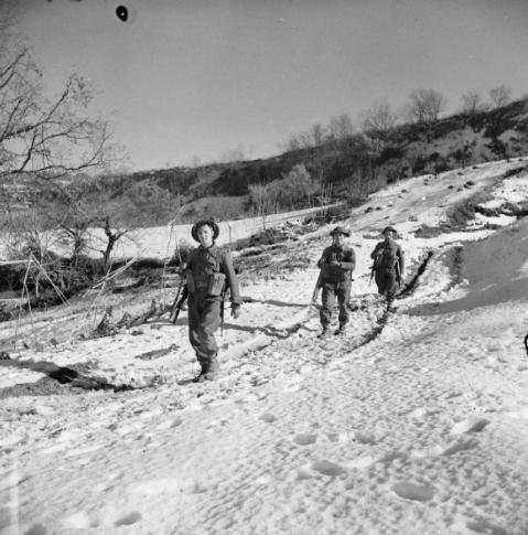 Men of the 1st Battalion Green Howards trudge down a snow-covered hillside, 1 January 1944. © IWM (NA 10626)