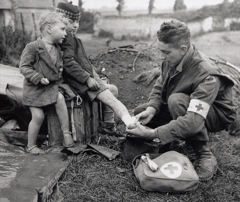 Lance Corporal W.J. Curtis, Royal Canadian Army Medical Corps, fixes the burned leg of a French boy, while his young brother looks on. Between Colomby-sur-Thaon and Villons-les-Buissons, Normandy, 19 June 1944. Photo by Ken Bell. Department of National Defence / National Archives of Canada, PA-141703.