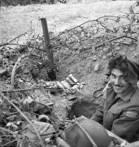 Private R.L. Randolf of the 1st Battalion, The Canadian Scottish Regiment, sits in a trench with a two-inch mortar, France, 12 June 1944. Credit: Lieut. Donald I. Grant / Canada. Dept. of National Defence / Library and Archives Canada / PA-131431.