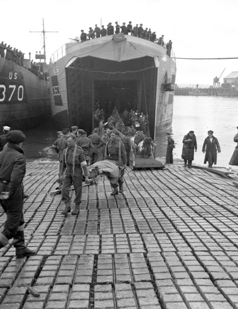 Canadian soldiers who were wounded in the Normandy beachhead being carried off a Landing Ship Tank (LST), Southampton, England, 8 June 1944. Credit: Lieut. Michael M. Dean / Canada. Dept. of National Defence / Library and Archives Canada / PA-131437