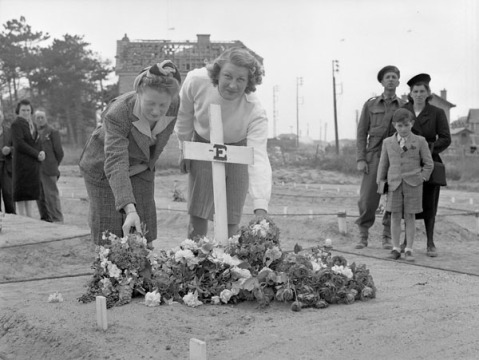 Two French women placing flowers on the grave of a Canadian soldier, Bernières-sur-Mer, France, 18 June 1944. Credit: Lieut. Frank L. Dubervill / Canada. Dept. of National Defence / Library and Archives Canada / PA-169264