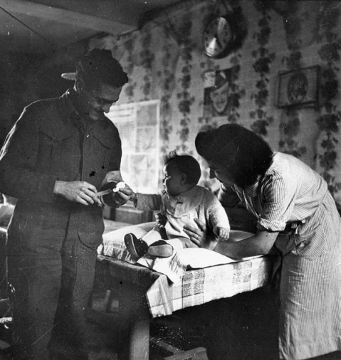 Captain Earl Bourbonnais, 23rd Field Ambulance, Royal Canadian Army Medical Corps, inoculating Nicole Pierre, Basly, France, ca. 27-28 June 1944. Credit: Lieut. Ken Bell / Canada. Dept. of National Defence / Library and Archives Canada / PA-190148