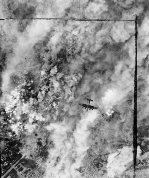 A Handley Page Halifax of No. 4 Group flies over the suburbs of Caen, France, during a major daylight raid to assist the Normandy land battle during Operation CHARNWOOD. 467 aircraft took part in the attack, which was originally intended to have bombed German strong points north of Caen, but the bombing area was eventually shifted nearer the city because of the proximity of Allied troops to the original targets. The resulting bombing devastated the northern suburbs. Royal Air Force official photographer. This is photograph CL 347 from the collections of the Imperial War Museums (collection no. 4700-19)