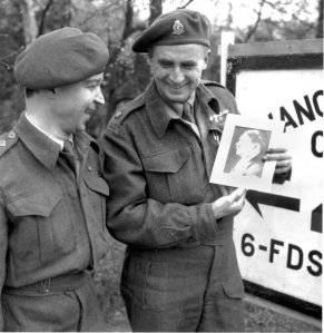 Doc Alexander and one of his officers have a laugh at Hitler's expense in April 1945. They found the photo in a convent. The sign in the background points in the direction of the 6 FDS (6th Field Dressing Station), which he commands.