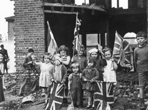 Children waving flags on VE Day, 8 May 1945. 'In bomb scarred Battersea, the little Londoners celebrated V E Day among the ruins of their homes'.