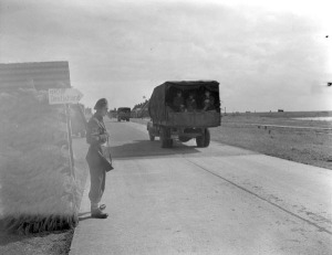 Gunner H.E. Robertson on guard duty as a convoy of German vehicles crosses the Zuiderzee causeway en route to Germany. Netherlands, 27 May 1945. LAC.