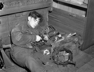 Private Robert A. Boicey of the Signals Platoon, 1st Canadian Parachute Battalion, cleaning his weapon in a German home, Lembeck, Germany, 29 March 1945. LAC.