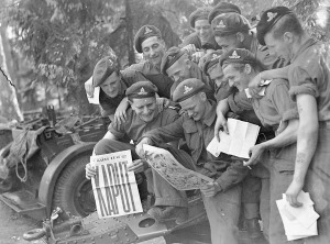 Gunners of the 12th Field Regiment, Royal Canadian Artillery (R.C.A.), with the Victory issue of the Maple Leaf newspaper, Aurich, Germany, 20 May 1945. LAC.