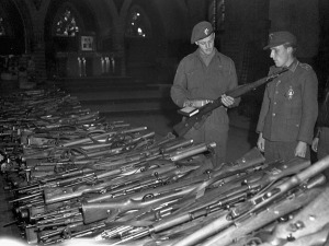 Unidentified German soldier turning in his rifle to a Canadian soldier, IJmuiden, Netherlands, 11 May 1945. LAC.