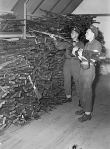 Privates J.A. Taylor and J.D. Villeneuve of the Royal Canadian Regiment stacking rifles turned in by surrendering German soldiers, IJmuiden, Netherlands, 11 May 1945.