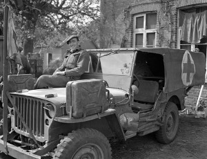 Private F.J. Dunn resting on his ambulance jeep while evacuating casualties south of Bad Zwischenahn, Germany, 29 April 1945.  LAC.