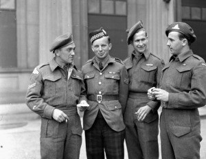 Corporal T.C. Mackenzie, Sergeant R.W. Williams, Private N.E. Smith and Gunner H.D. Gugell, who all received Military Medals, at Buckingham Palace, London, England, 27 June 1945.  LAC.