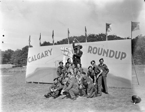"Entertainers and troopers of The Calgary Regiment in front of a sign reading ""Calgary Roundup"", an event which included sports, entertainment, refreshments, and the presentation of a silver service to the regiment's commanding officer, Apeldoorn, Netherlands, 18 June 1945.  LAC."